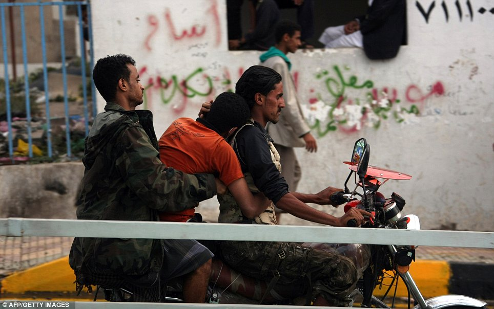 Emergency aid: Yemeni medics take an injured protester on a motorcycle to the hospital