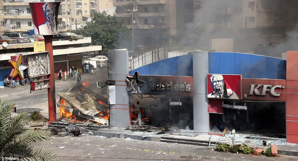 In flames:the violence loving muslim gang try 2 attack the pope but settle for halal kfc instead.of  A Hardee's and a Kentucky Fried Chicken (KFC) fast food outlet burns after protesters set the building on fire in Tripoli, northern Lebanon