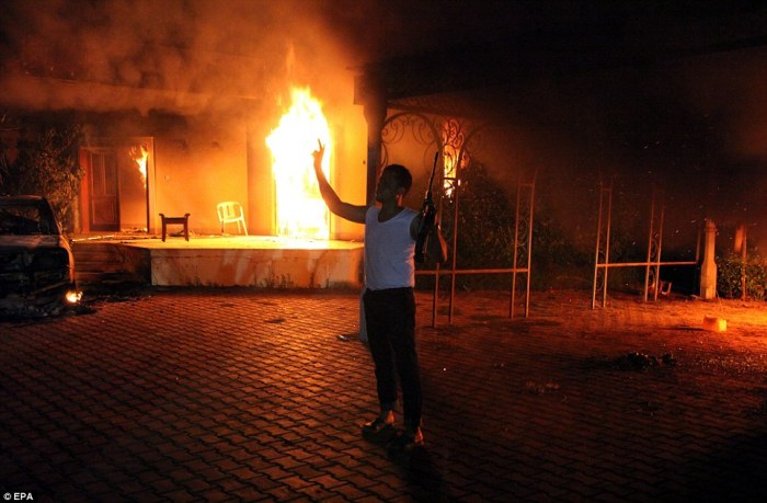 Attacked: An armed man holds his rifle as he stands next to buildings set on fire at the US consulate, in Benghazi, Libya, September 11