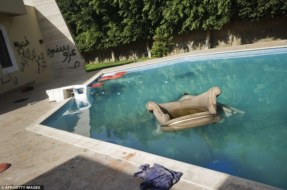 Sinking: An armchair and furniture float in the swimming pool of the US consulate in Benghazi on Thursday