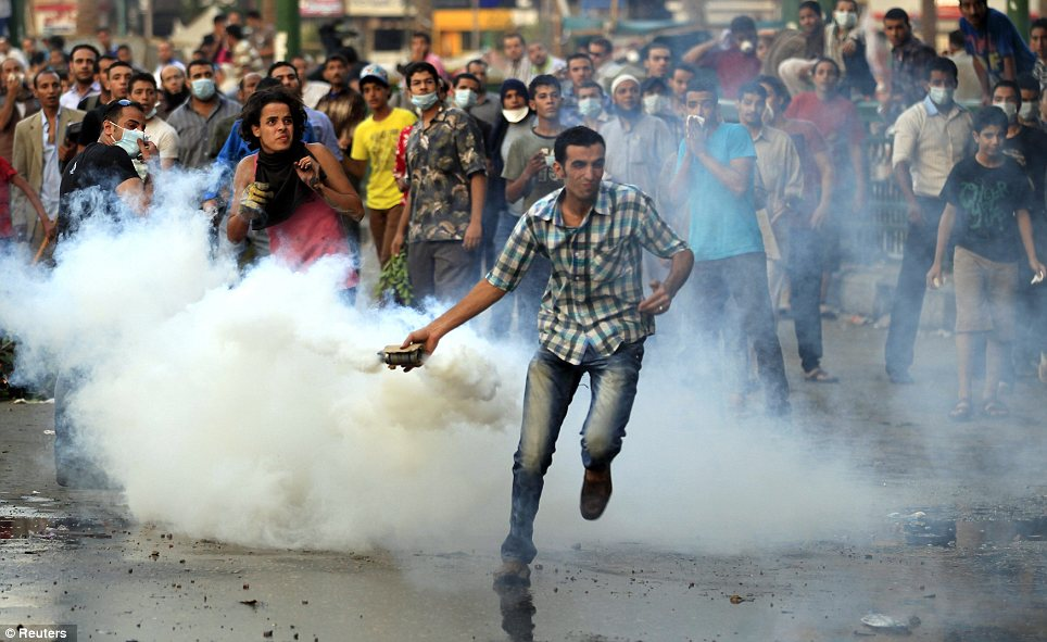 Clashes:even egyptian transvestites get in on the orgy of violence. the muslim mob hellbent on violence and destruction throws a tear gas canister, which was earlier thrown by riot police, during clashes along a road which leads to the U.S. embassy, near Tahrir Square in Cairo yesterday