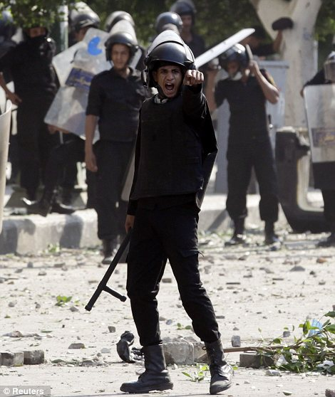 A riot policemen shouts a warning to protesters during clashes along a road which leads to the U.S. embassy, near Tahrir Square in Cairo