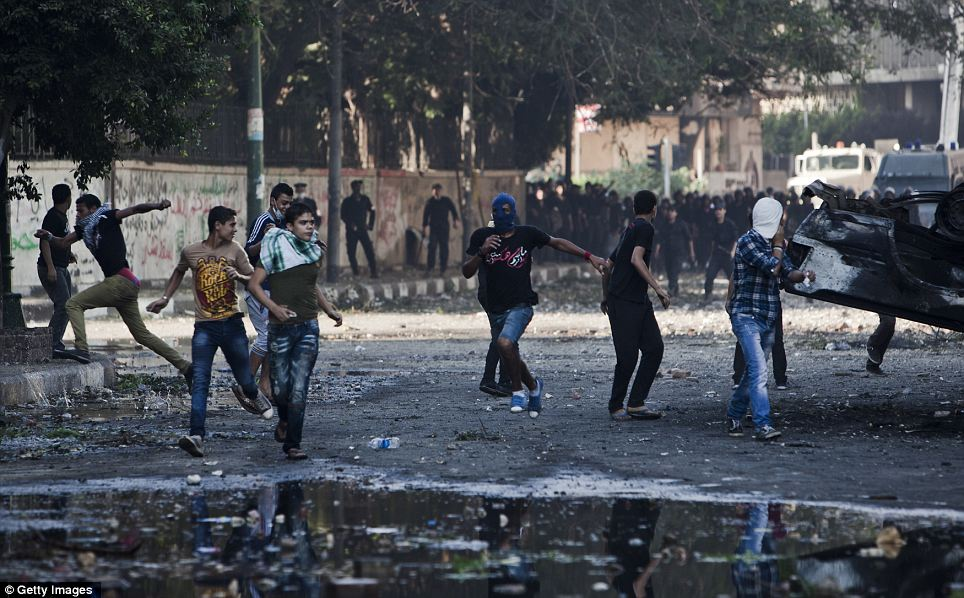 Street fight: Protesters in Cairo appeared to answer the Brotherhood's call to arms this morning as thousands advanced on the US embassy near Tahrir Square to be met by a phalanx of heavily-armed riot police in a second day of chaos to blight the city