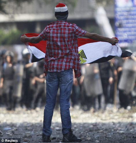 Ban the film: A protester shouts slogans as he waves an Egyptian flag before a line of riot police