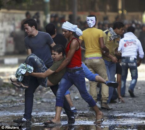 Protesters carry an injured man: As the violence continued throughout the morning, the Egypt's president Hosni Mubarak appealed for calm on live television