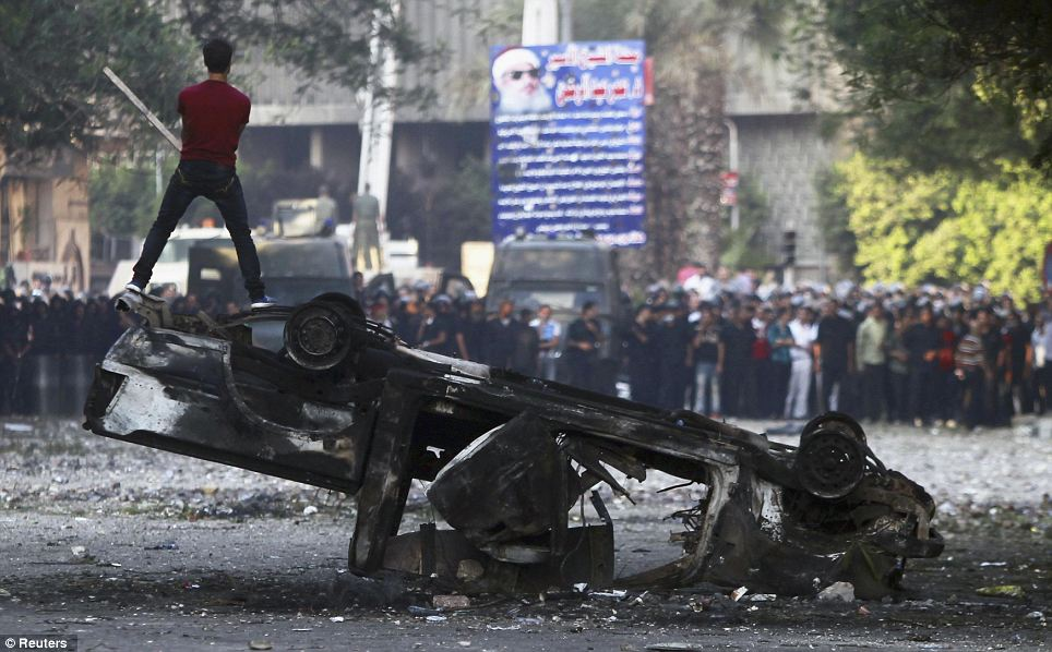Stand off: A defiant protester taunts the police phalanx from the top of an upturned and burned-out car