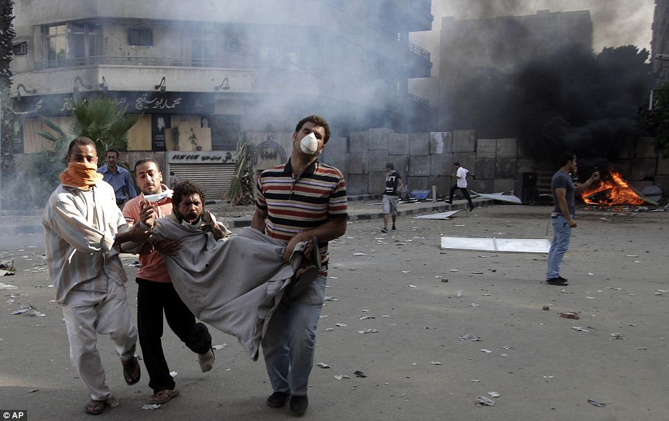 Egyptian muslim thugs hellbent of violence carry an injured comrade from the site of clashes with security forces, unseen, near the U.S. embassy in Cairo