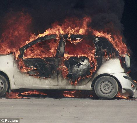 A burning car is seen during a demonstration in front of the U.S. Embassy in Tunis