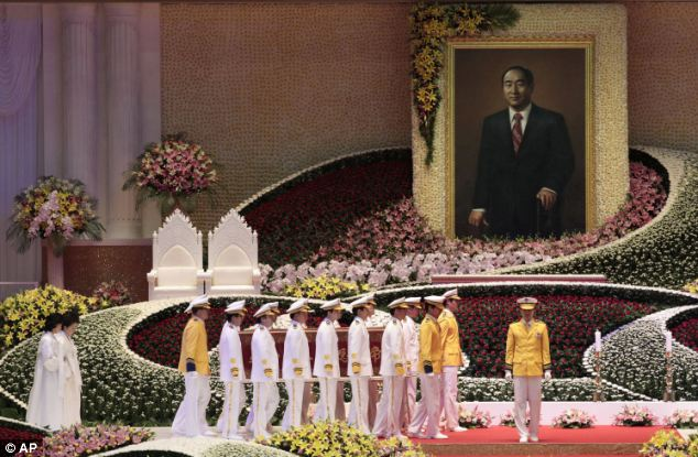 Ornate display: A giant image of the late founder was displayed at the service in front of hundreds of flowers