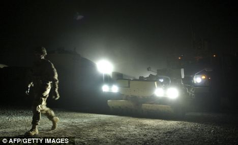 An Infantry man from the 1st platoon walks in front of a tactical mine-resistant vehicle in Kandahar province