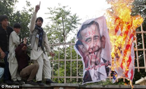 Continuing unrest: Afghan protesters set fire to a U.S. flag and shout slogans during a demonstration in Kabul