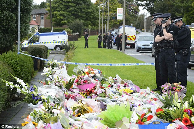 Crestfallen: Emotional police officers stand by a floral tribute near the scene where two female police officers were shot