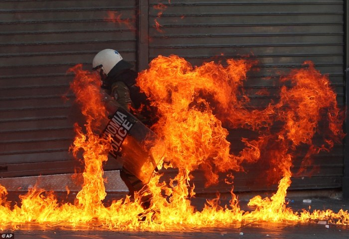 On fire: A riot officer battles to extinguish flames from a petrol bomb, thrown at police during a demonstration in Athens which descended into violence today