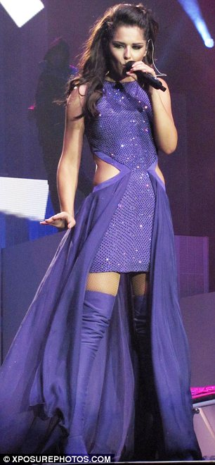 Cheryl to the rescue: The singer looked like a superhero in a flowing purple gown with over-the-knee boots