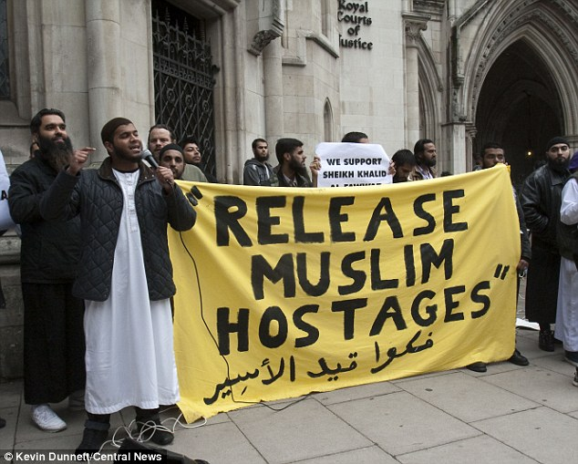 'Release The Muslim Hostages': Supporters of Abu Hamza hold up a huge banner while one talks to the crowds outside the Royal Courts of Justice on a microphone