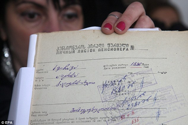 Soviet-era: A Georgian local official shows a document with the birth date of Mrs Khvichava in Sachino