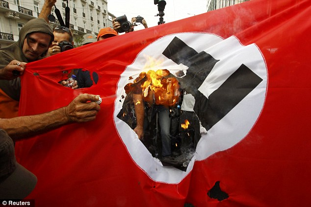 Fuelling the flames: Demonstrators burn a flag emblazoned with a swastika during the visit of German Chancellor Angela Merkel