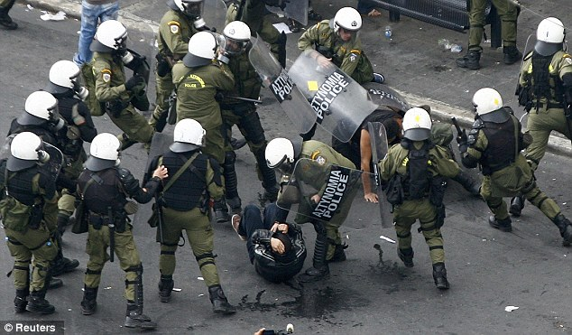Surrounded: The protester on the ground is quickly swamped by riot police