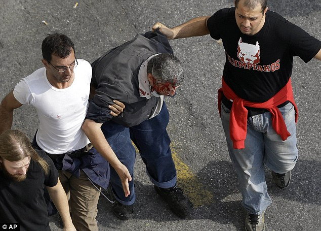 Walking wounded: Protesters assist an injured demonstrator during clashes in front of the parliament