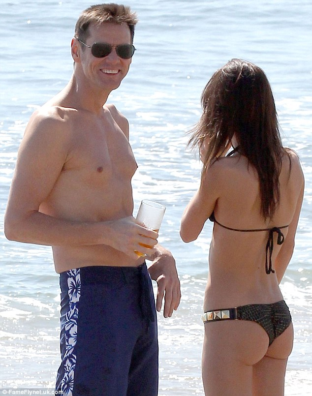 A cheeky smile: Jim certainly looked pleased with himself as they enjoyed a beach date in Malibu last month