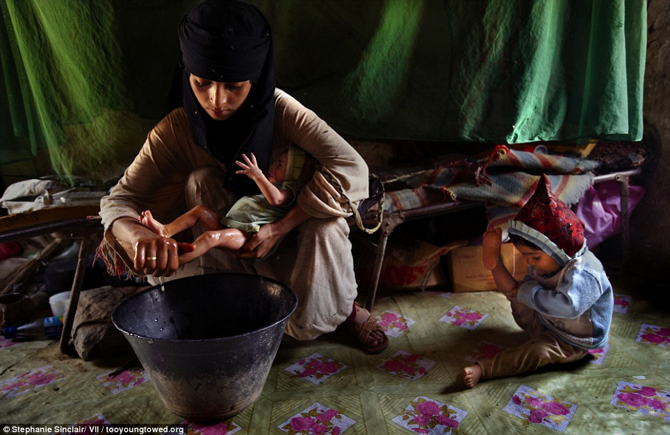 Child mothers: Asia, a 14-year-old mother, washes her new baby girl at home in Hajjah while her two-year-old daughter plays