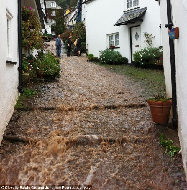 Waterfall: A cobbled street in Clovelly, North Devon turns into a torrent flood after a bank burst on Friday