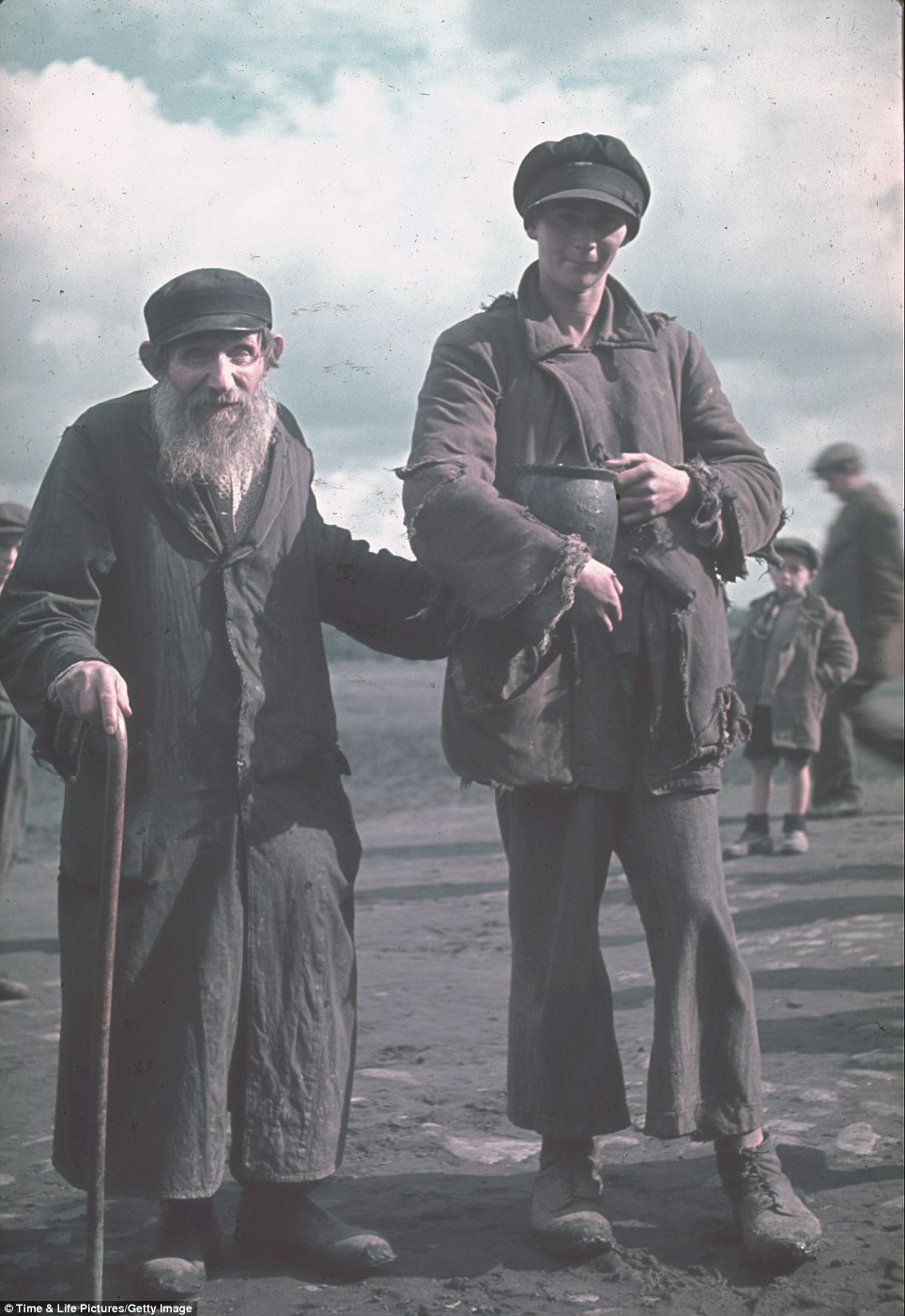 A young woman clutches a jug as she escorts an elderly Jewish man through the Kutno Ghetto in early 1940