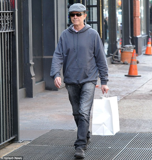 Dressed down: Bowie kept his head down as he stepped out, wearing a casual outfit of a hooded sweatshirt, jeans, flat cap and sunglasses