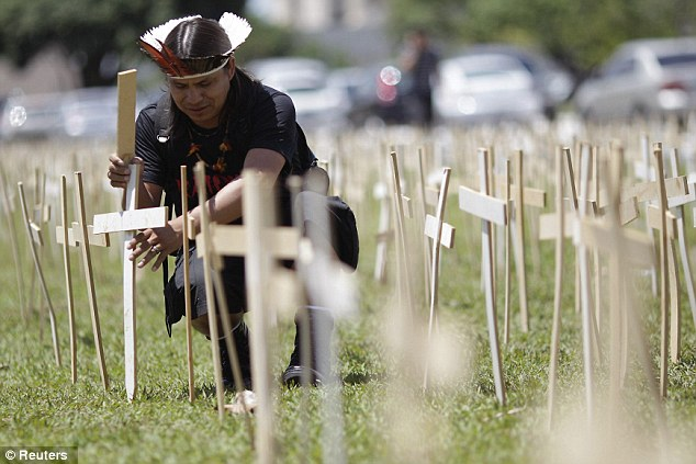 Protest: An ethnic Guarani-Kaiowa Brazilian Indian from the state of Mato Grosso do Sul fixes a cross into the lawn at the Esplanade of Ministries in Brasilia