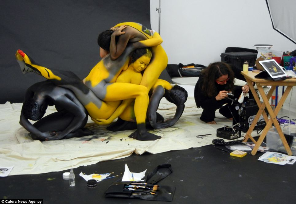 Beautiful bodywork: The models hold their poses while Ms Merry accessorises with a final lick of paint