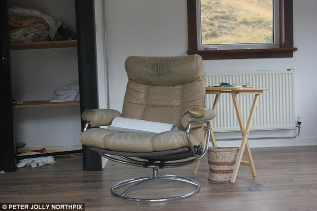 Eerie: Savile's chair, a dented bin and some of his possessions strewn about the room