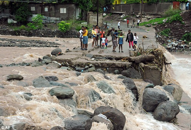 Residents stand on a bridge that was previously destroyed in 2008 by Tropical Storm Gustav, while watching Hope River swell in the village of Kintyre, near Kingston, Jamaica today