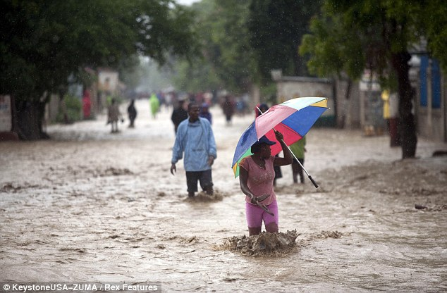 Natural disaster: A woman walks across a flooded street after hurricane Sandy hit Port Au Prince in Haiti