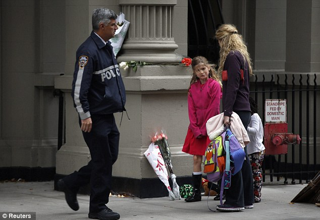 Distress: On Friday morning, a woman and two children visit the apartment where the youngsters were killed