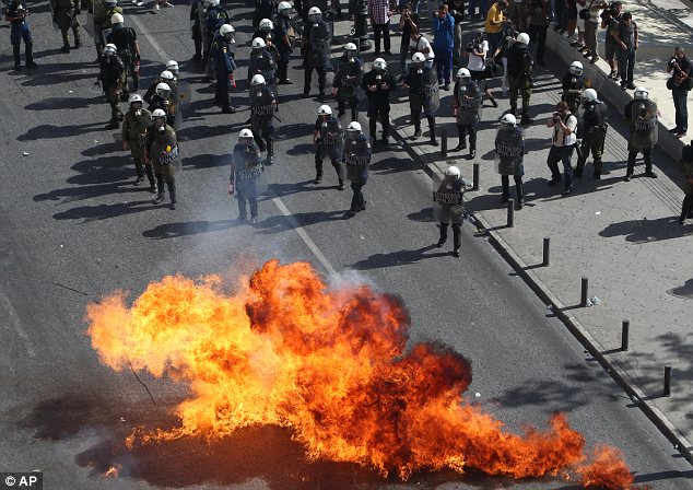 Flare-up: Protesters throw petrol bombs against riot police in Athens today during a 24-hour general strike