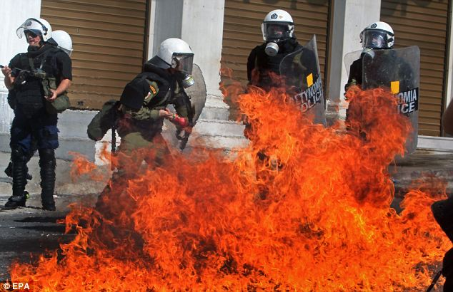 Wall of fire: Riot police are engulfed in flame by a petrol bomb thrown by protesters. Greek trade unions called a 24-hour general strike to oppose new austerity measures just last week