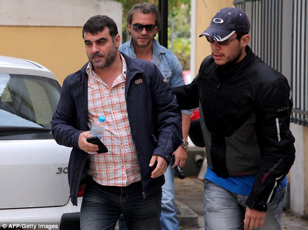 Led away: Kostas Vaxevanis was giving a radio interview in Athens when officers stormed into the studio saying he had to cut the segment short 'to be arrested'