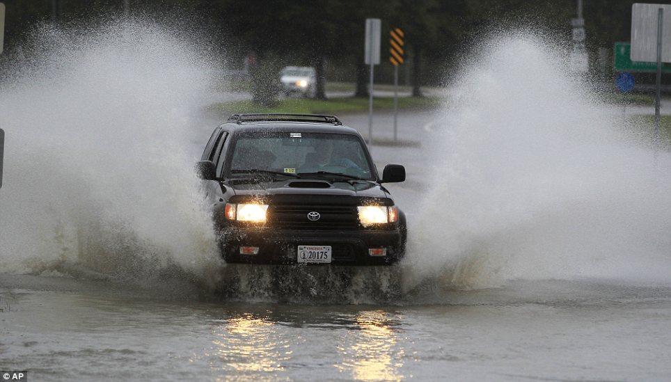 En su camino: Un coche se mueve a través de una calle inundada en Norfolk, Virginia después del impacto del huracán arena