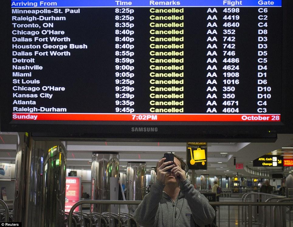 No hay escape: Un viajero toma imágenes de un monitor de vuelo que muestra vuelos cancelados en el aeropuerto de La Guardia en Nueva York el domingo por la noche