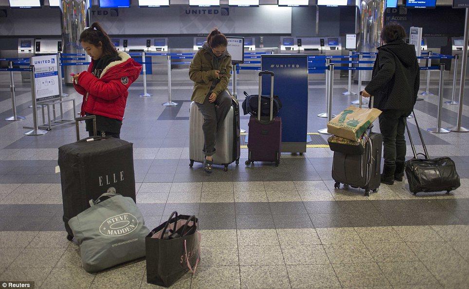 Mucho tiempo de espera: Los viajeros procedentes de Corea del Sur busca de información en sus teléfonos móviles el lunes después de llegar a un terminal vacío como los vuelos en el aeropuerto de LaGuardia en Nueva York fueron cancelados