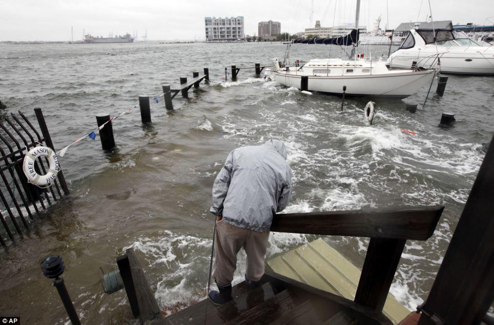 Inspección de la tormenta: Jack Devnew mira el agua que cubre un muelle mientras se comprueba en su barco en un puerto deportivo cerca del centro de Norfolk, Virginia