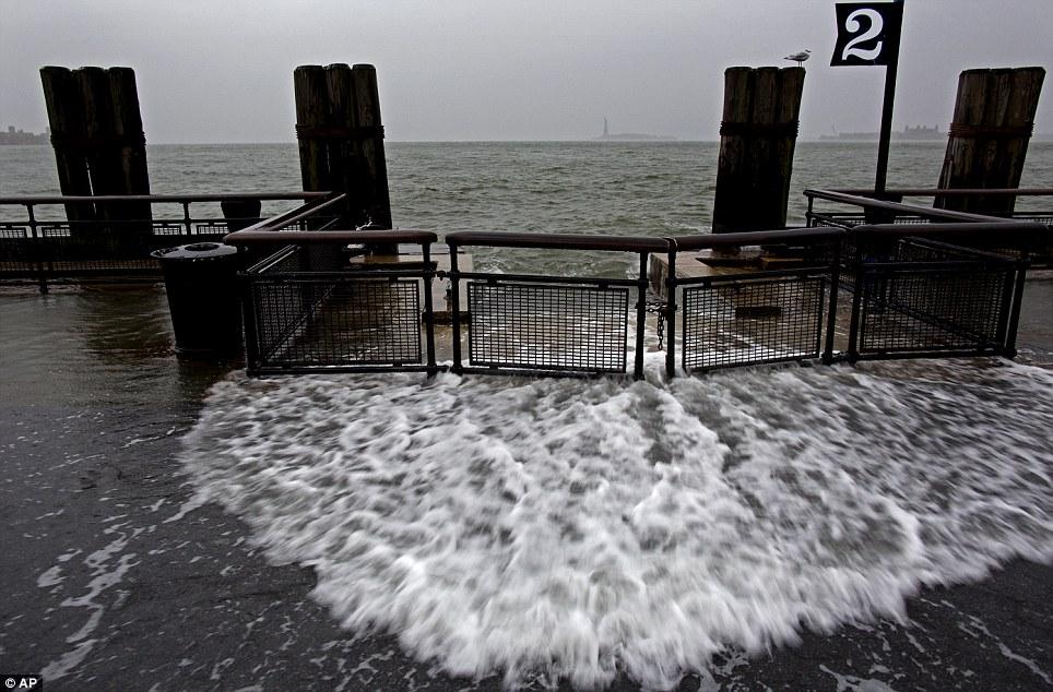 Las mareas altas: Olas pasen sobre la pared del mar cerca de la marea alta en Battery Park en Nueva York esta mañana