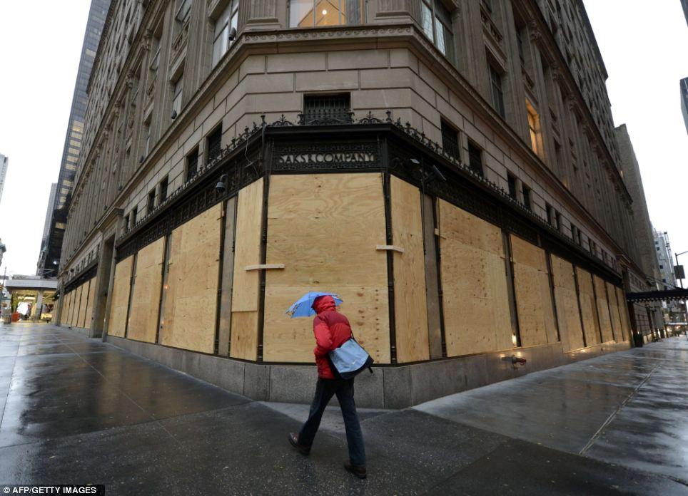 Vacío: Una mujer pasa junto a un tapiadas Saks Fifth Avenue neoyorquinos a prepararse para el huracán de arena que llega a la ciudad esta noche