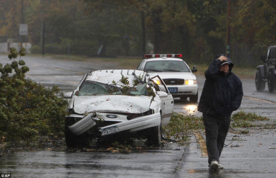 Havoc: Un coche aplastado por un árbol caído se encuentra a lo largo de la carretera de Montauk como se acerca el huracán Sandy en Bay Shore, Nueva York