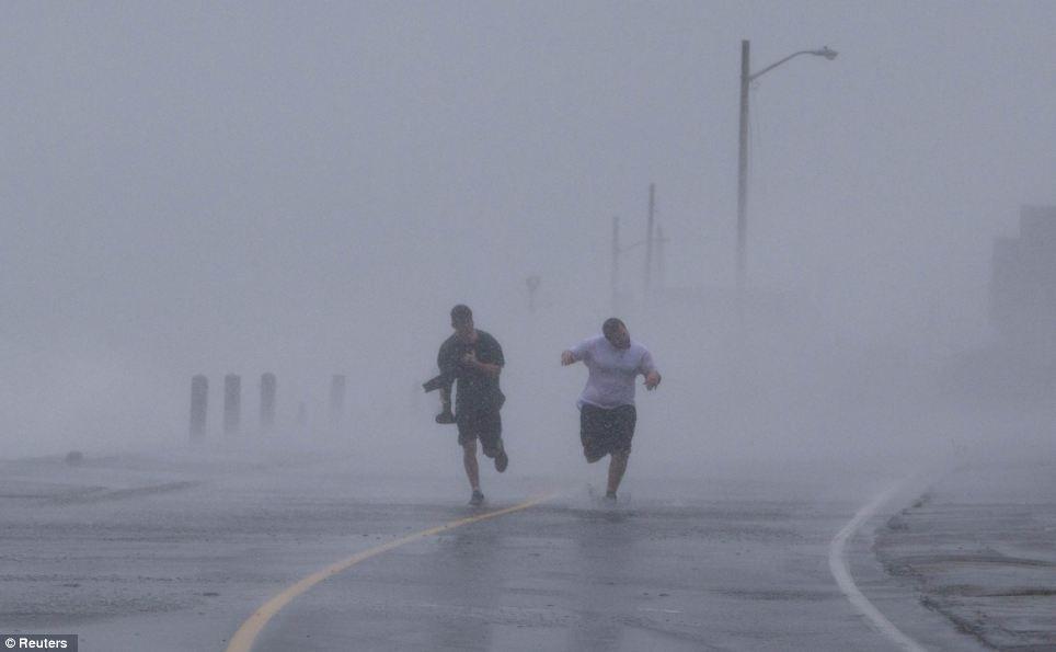 Yendo por la seguridad: Dos muchachos corren para esquivar los fuertes vientos y las olas de los efectos del Huracán Sandy en Marshfield, Massachusetts