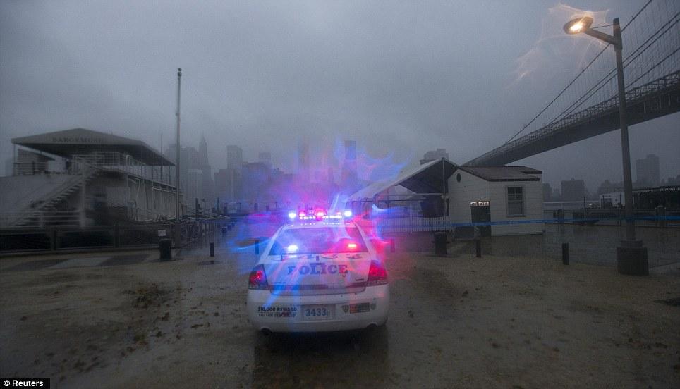 A lo largo de la línea de costa: Un coche patrulla de la policía frente al mar en Brooklyn, Nueva York esta noche como arena azota la Gran Manzana
