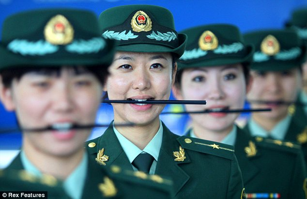 Smile Chinese style: During the 'how to smile' course in Dalian, Liaoning Province, China, customs police were made to practise by holding a chopstick between their teeth and smiling