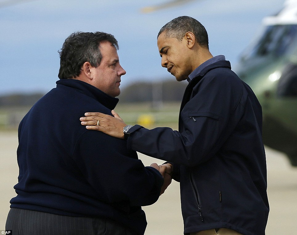Crossing the political divide: Barack Obama comforts the New Jersey's Republican Governor Chris Christie, a Mitt Romney supporter who has sung the President's praises since Superstorm Sandy struck