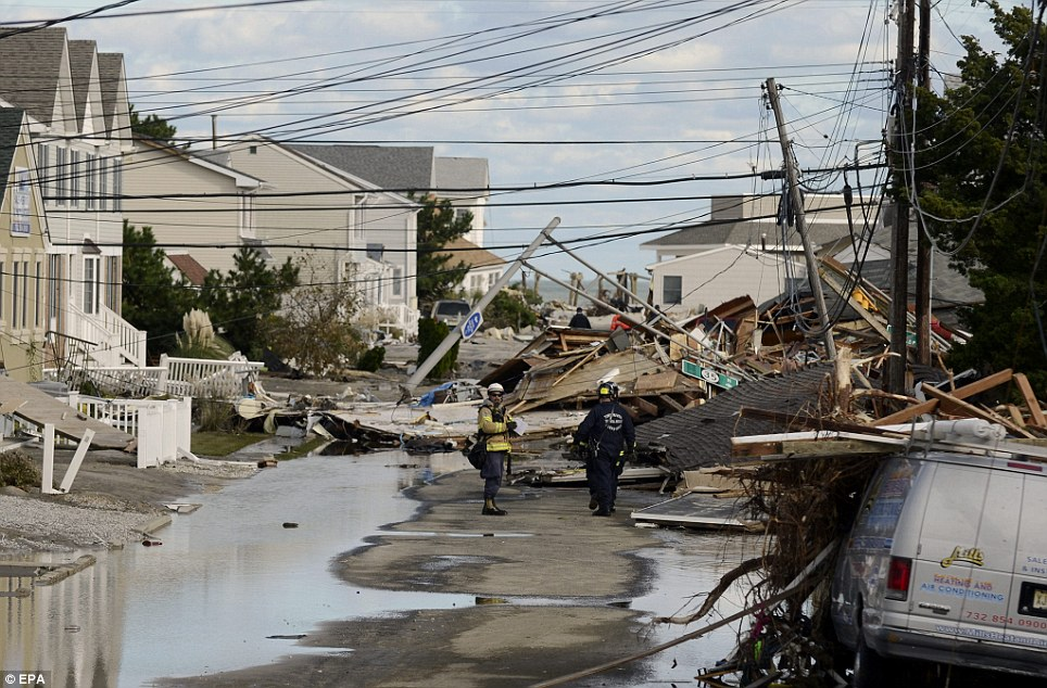 Major problem: Emergency workers attend homes heavily damaged by Superstorm Sandy in Seaside Heights, New Jersey. A van is stuck under debris in the foreground