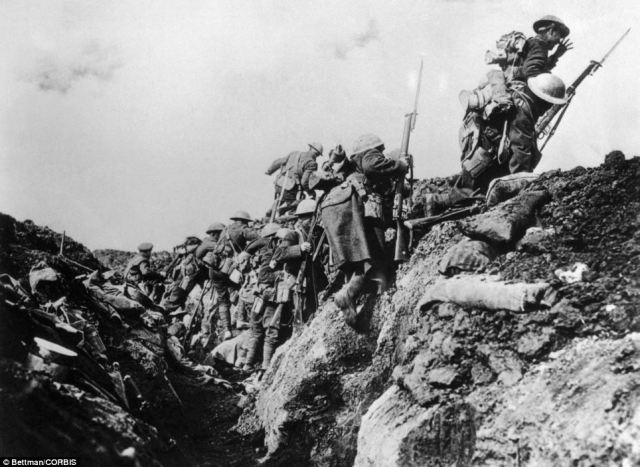 Soldiers emerge from a trench and go over the top into battle during the First World War